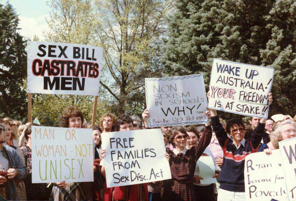 Colour photo showing women and a couple of men protesting. Many are holding placards saying things like 'Sex bill castrates men', 'Free families from Sex Disc Act', 'Wake up Australia! Your freedom is at stake'. - click to view larger image