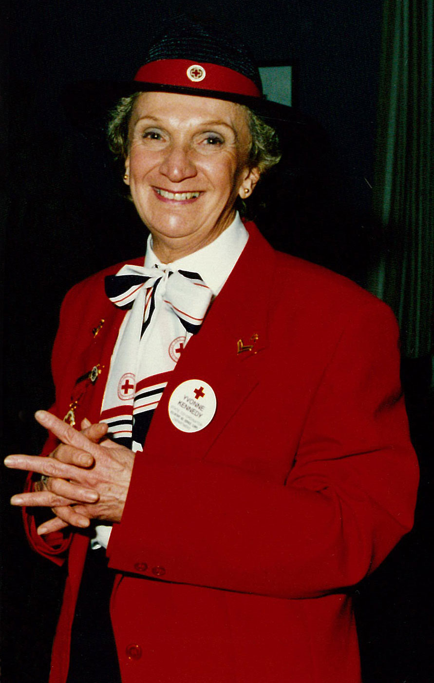 Portrait showing a woman wearing a red jacket and a black hat with red band and pin. The woman is smiling and wears several Red Cross badges and pins. - click to view larger image