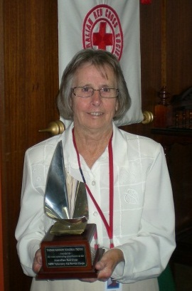 A woman stands at the centre of the image holding a trophy at her waist. The trophy has a curved metal feature on top of a wooden base, with a plaque reading 'YVONNE KENNEDY MEMORIAL TROPHY / Awarded for / the most outstanding contribution to the / Australian Red Cross / NSW Voluntary Aid Service Corps'. A Red Cross banner is partially visible in the background.