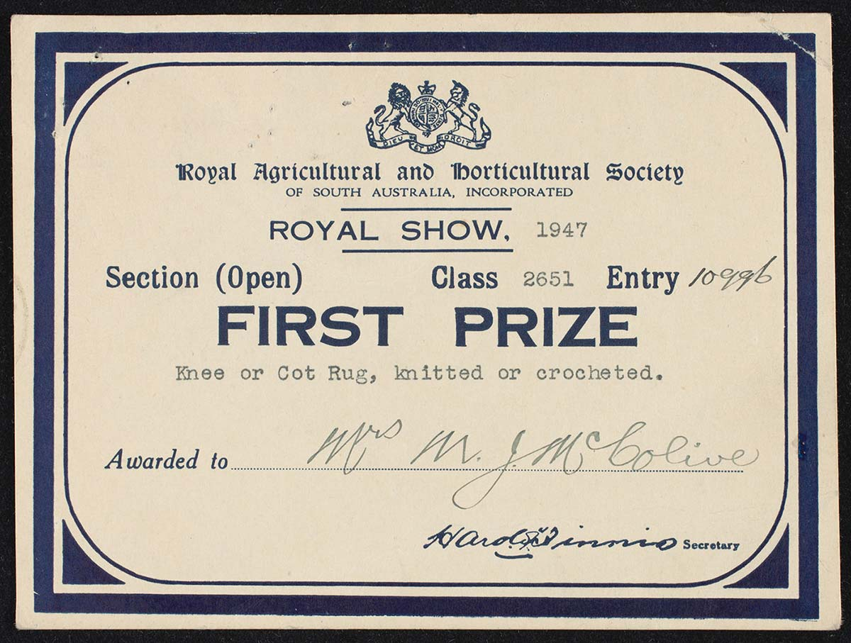 A photo of a first prize card from the 'Royal Agricuttural and Horticultural Society of South Australia', awarded to 'Mrs MJ McColive'  for 'Knee or Cot Rug, knitted or crocheted'.  - click to view larger image