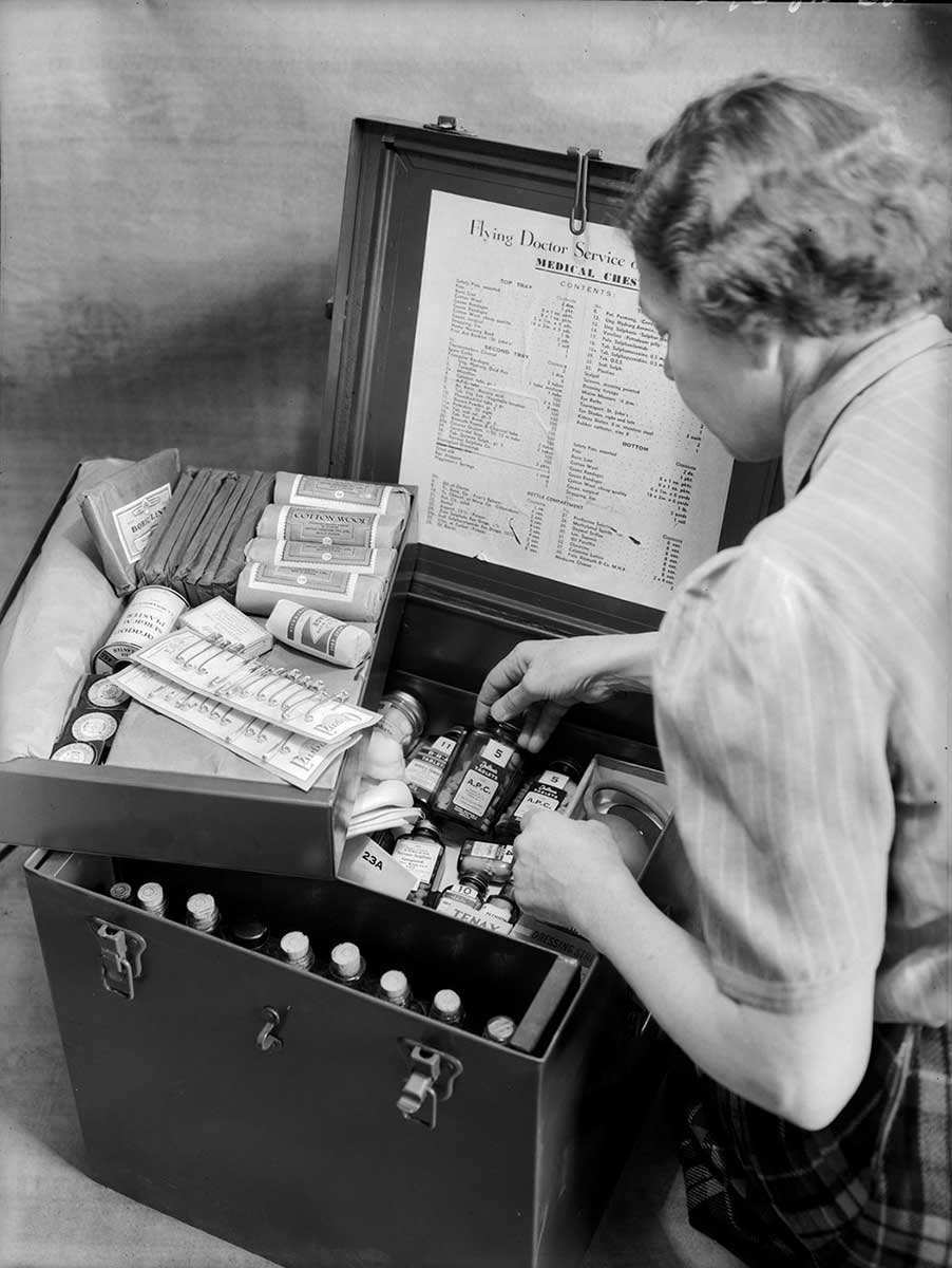 A woman sits on the floor examining the contents of a metal box.