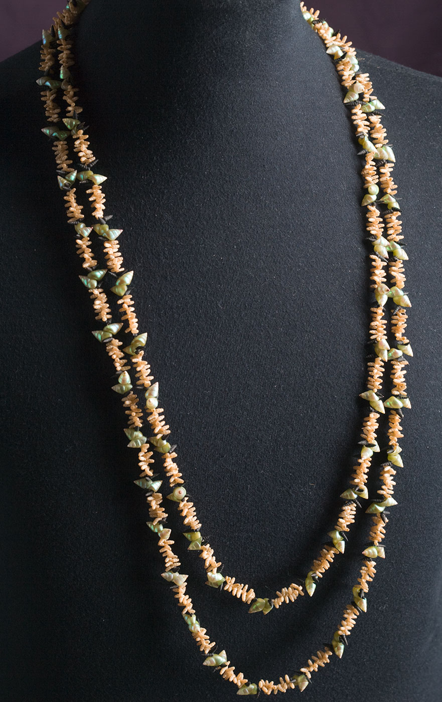 A necklace made from sea shells displayed on a dressmaker's dummy. - click to view larger image