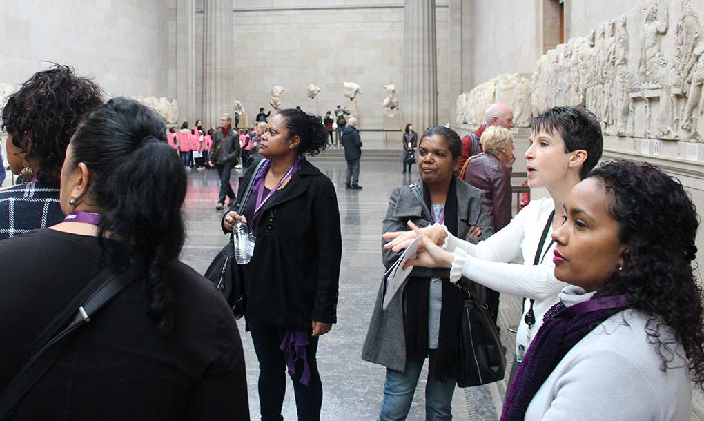 A female tour guide engages with a small group of women inside a museum. - click to view larger image