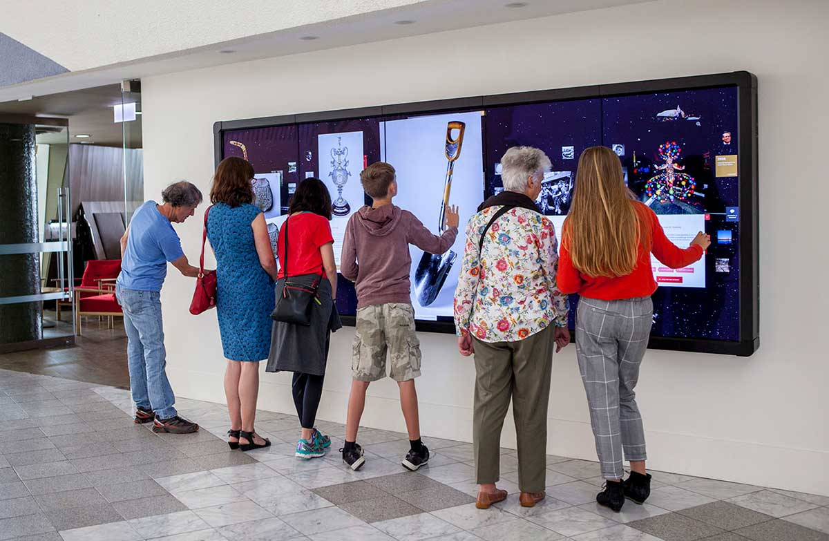 Group of people facing a large, digital screen covered with images and text.