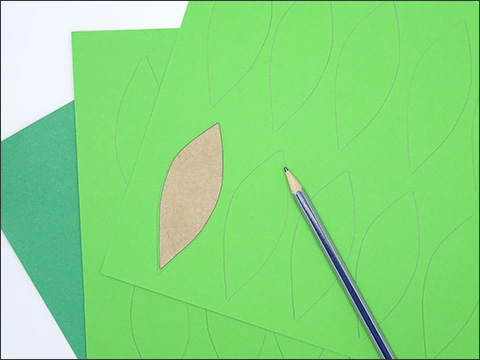 Two light green pieces of paper sit layered over a darker green piece of paper. There are leaf tracings on the top sheet with a led pencil placed on top.