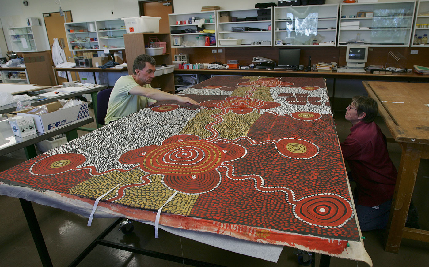 Two conservators work on either side of a large canvas by Uta Uta Tjangala. - click to view larger image