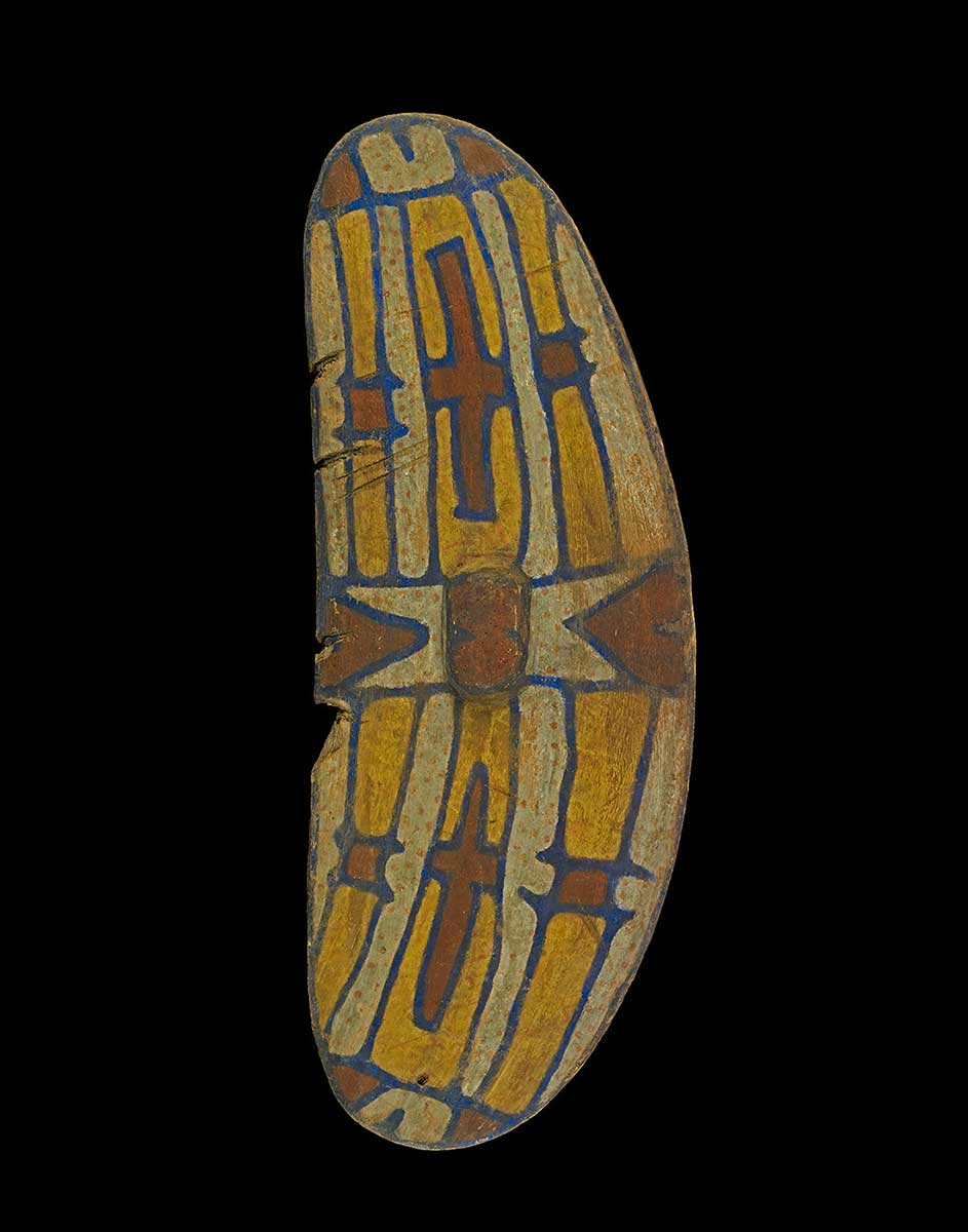 Oval shaped wooden shield with painted design in red, yellow, white and black. - click to view larger image