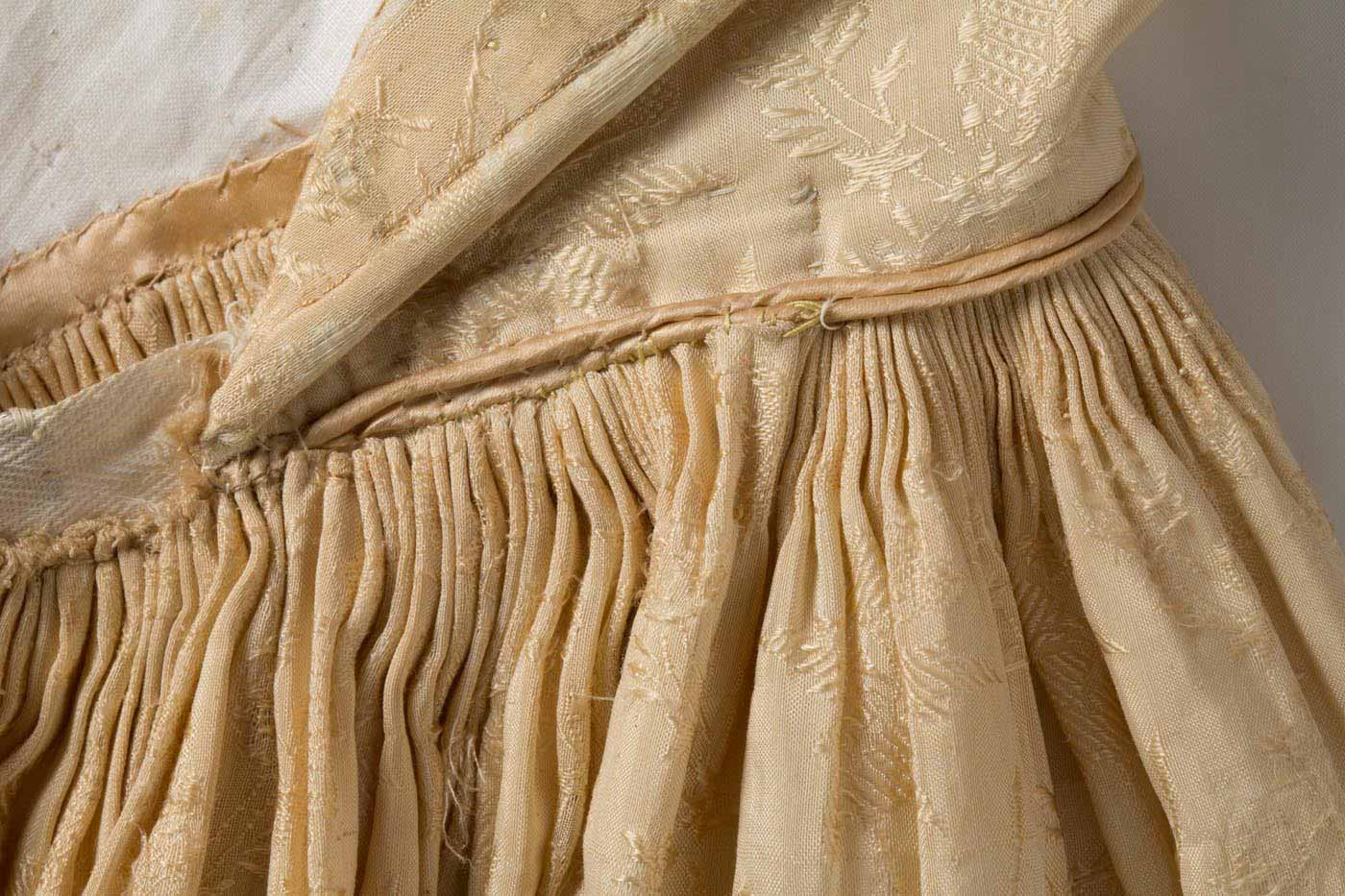 Back of dress with bodice undone, revealing the central boning and interior fine pleating at the waistline. - click to view larger image