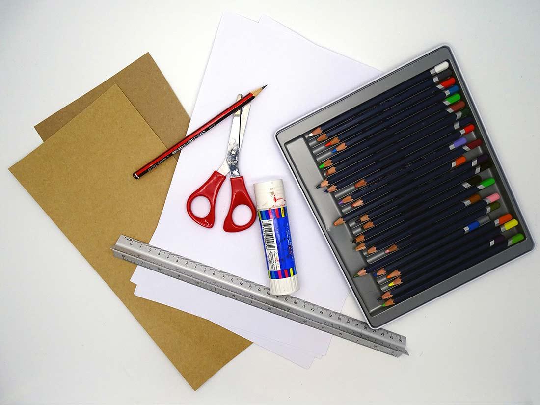 Arrangement of paper, cardboard, graphite pencil, colour pencils, glue, ruler and scissors