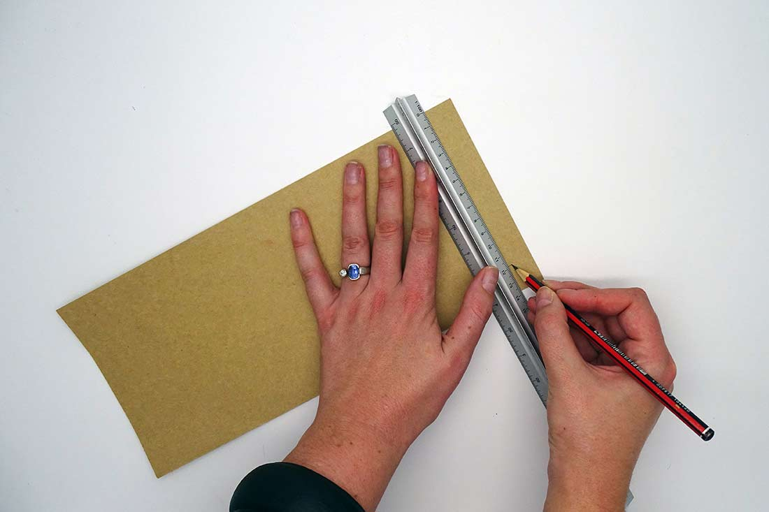 Two hands measuring cardboard with a ruler and pencil - click to view larger image