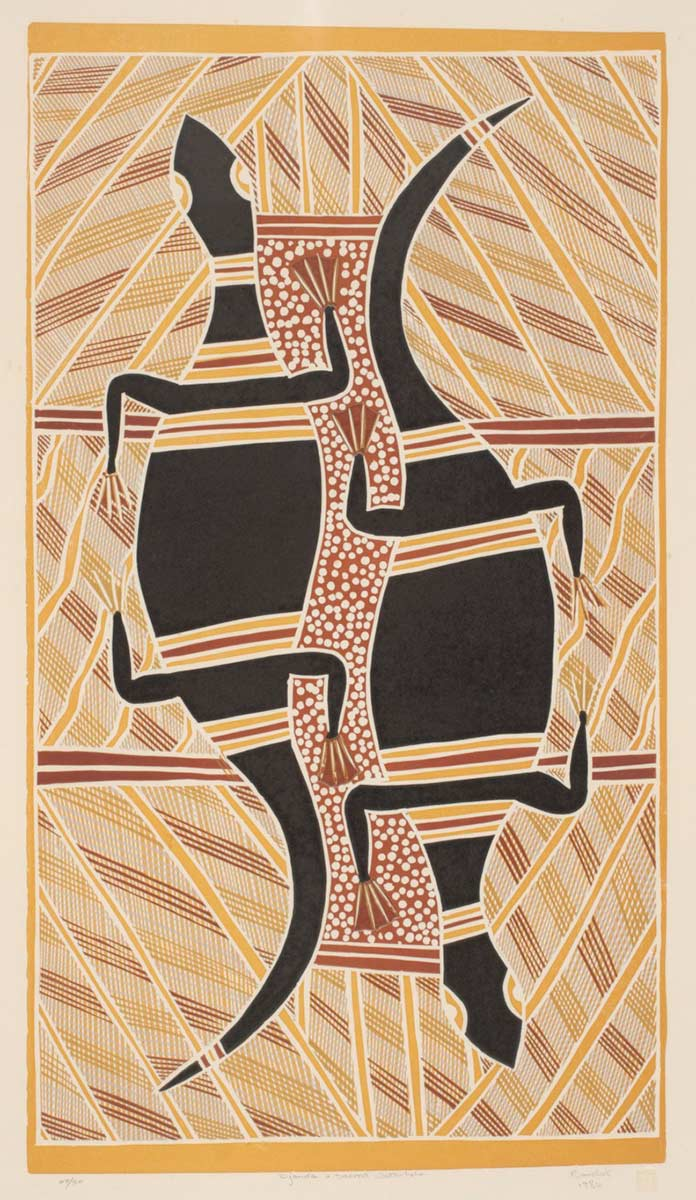 An Australian Indigenous linocut print on paper. The print is in portrait format ie the vertical sides are longer than the horizontal sides. It depicts what appear to be two goannas, next to each other but facing in opposite directions. The goannas are black with red and yellow bands across them. Between them is an area of red with a traditional white dot pattern. The remainder of the print is covered in traditional line patterns, in yellows, reds and ochres. - click to view larger image