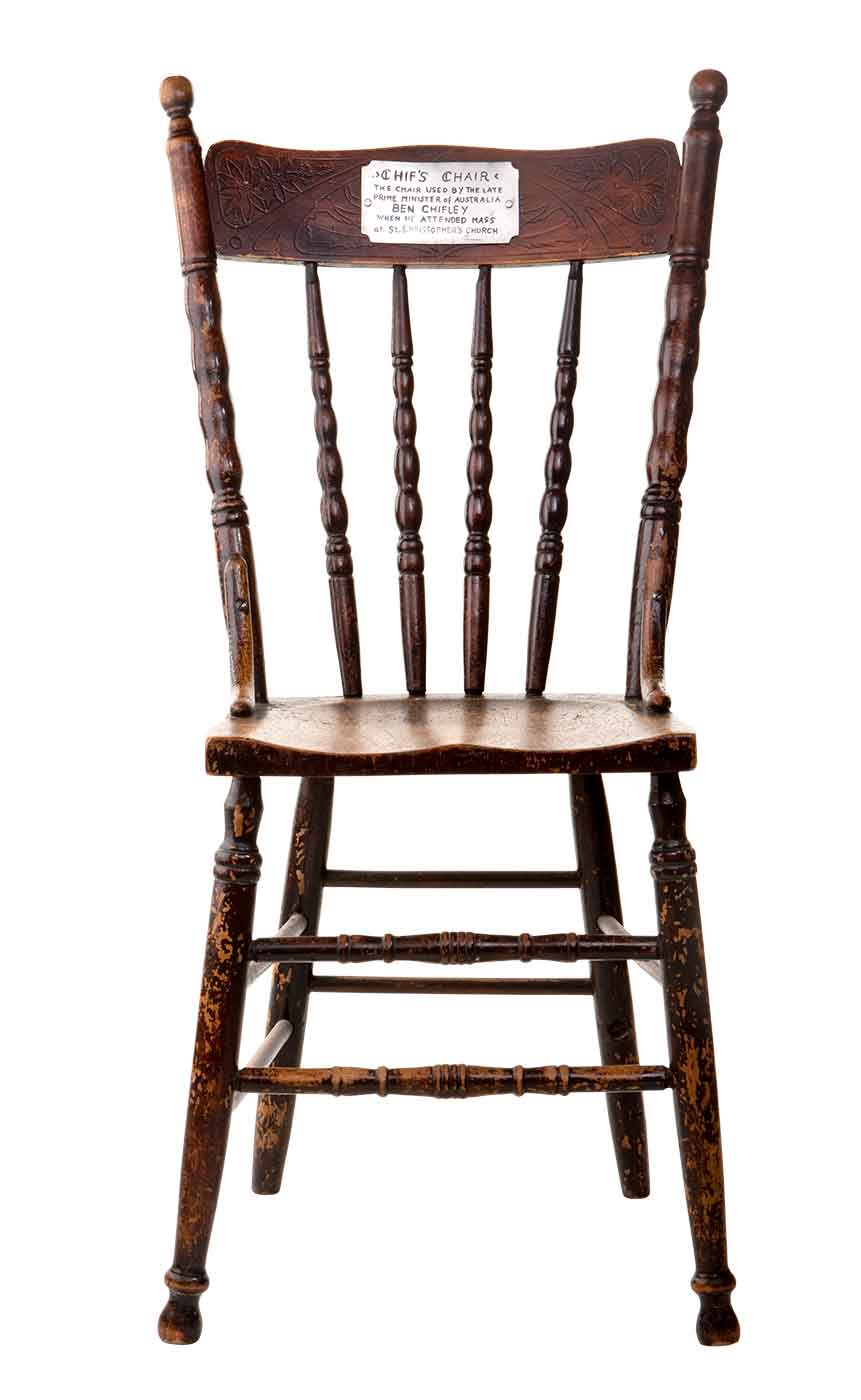 Wooden chair with silver plaque attached to back rest.