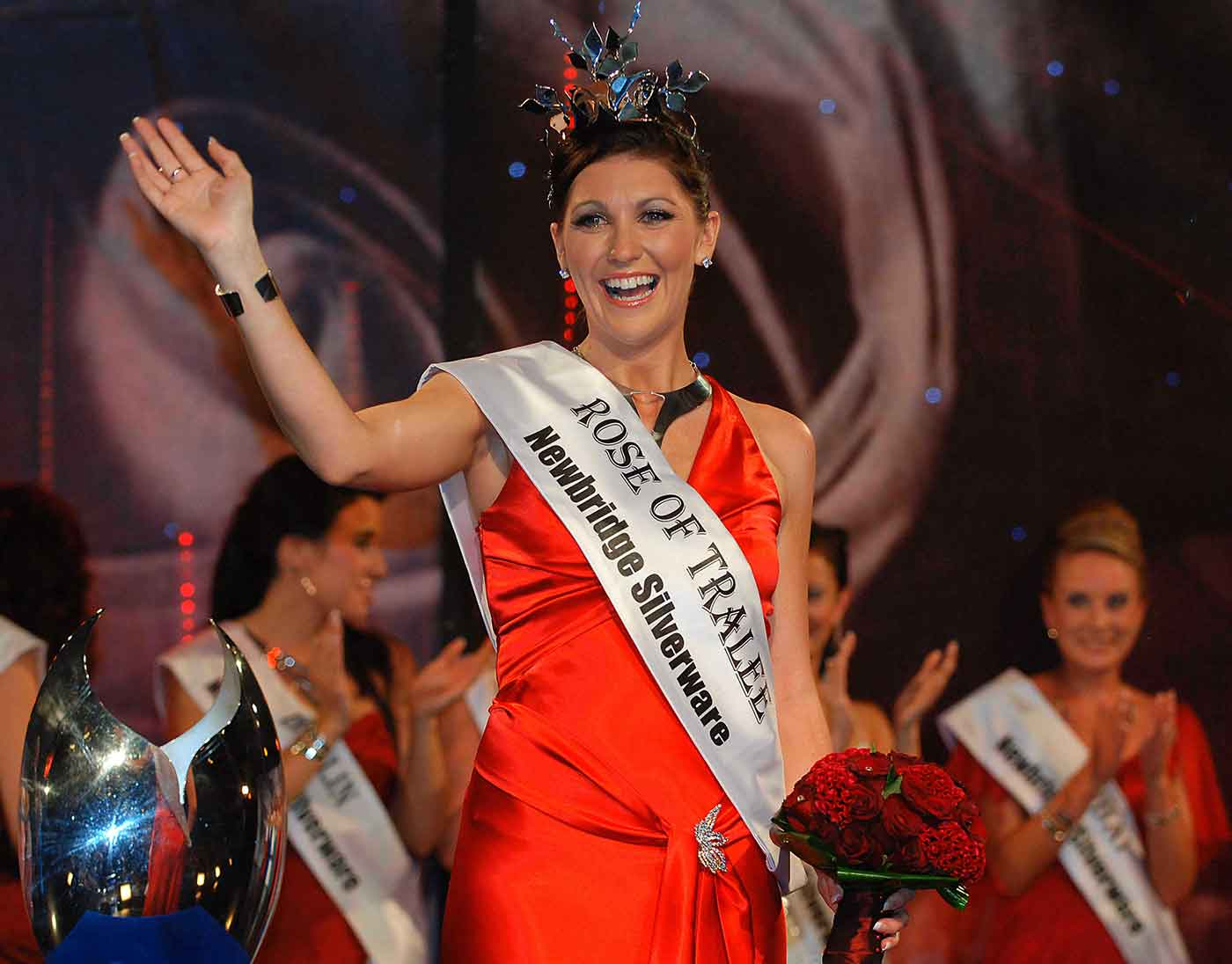 Woman wearing a satin or silk red dress, tiara and sash with the text: ROSE OF TRALEE, waving from stage with other contestants in the background. - click to view larger image