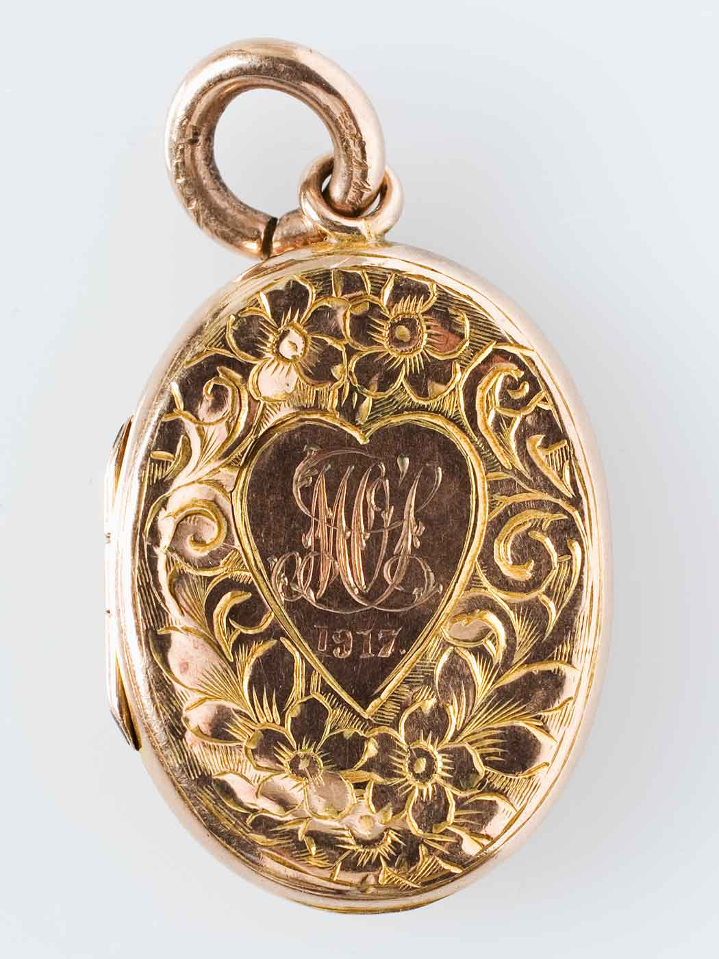 Golden locket with ornate design and the date 1917 engraved. - click to view larger image