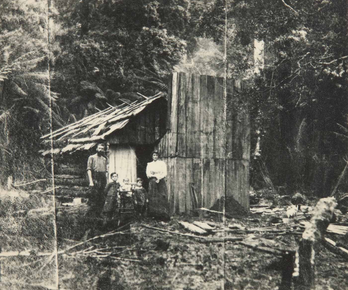 A black and white photograph showing a family standing in front of a small wooden log house. The family consists a man and a woman with two boys standing on either side of a baby in a high chair. The house is surrounded by dense bushland. - click to view larger image