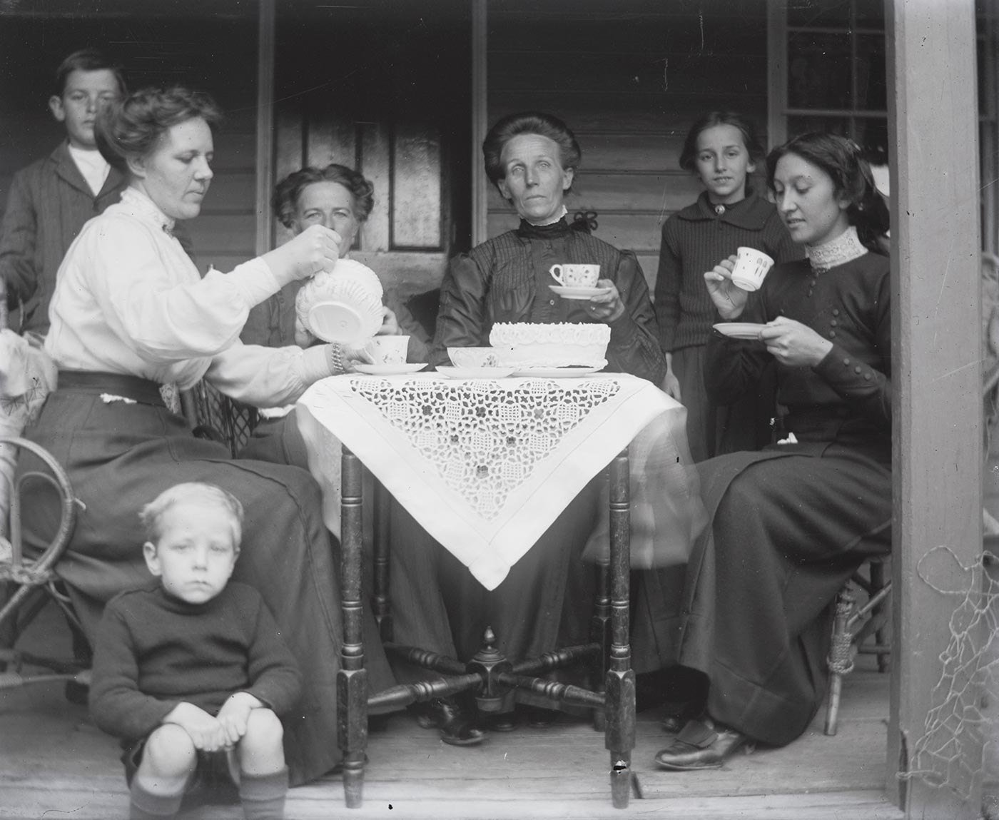 A photographic glass plate negative showing seven people having tea on a veranda. Four women are sitting at a small wooden table and a young boy is sitting on the edge of the veranda in the foreground. One of the women is pouring a cup of tea from the teapot. Another young boy and a young girl stand behind the women at the table. The table is covered with a lace tablecloth and holds teacups and a cake. - click to view larger image