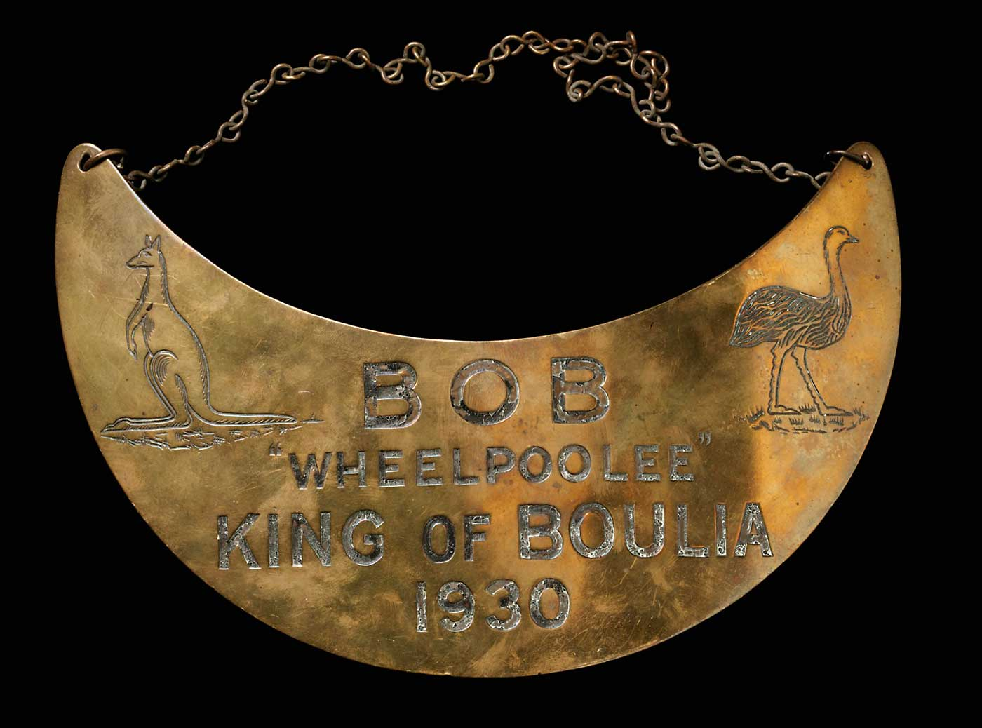 A crescentic, slightly convex brass breastplate with chain, engraved 'BOB / 'WHEELPOOLEE' / KING OF BOULIA / 1930' with a kangaroo on the left and an emu on the right. The chain is looped through two holes at the top of the breastplate.