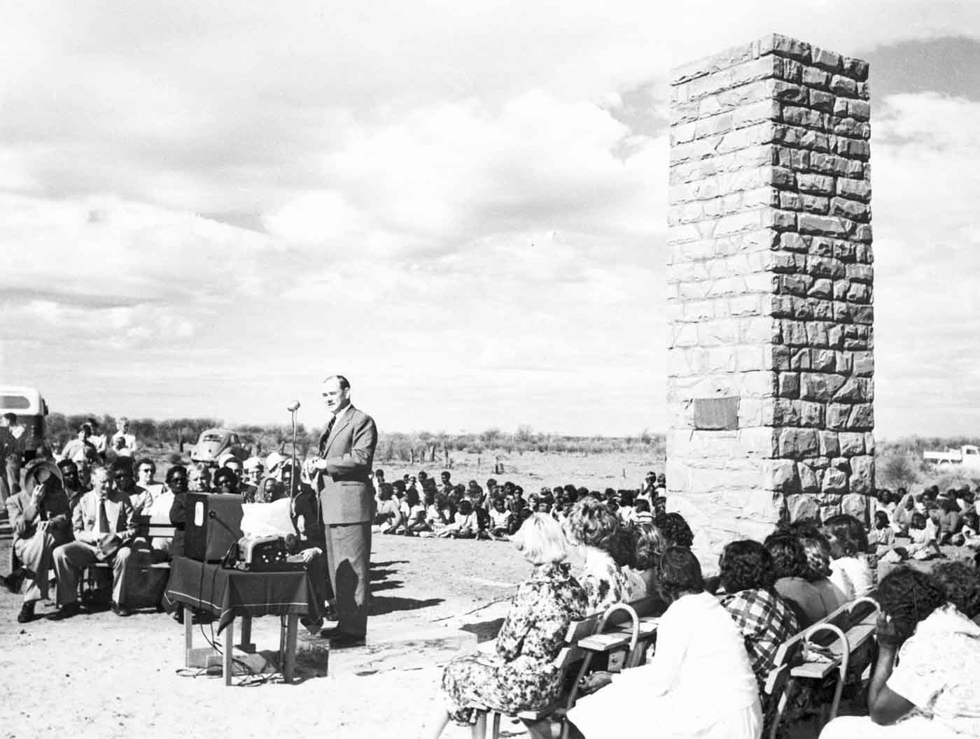 Black and white photo of a man speaking into a microphone and addressing a large seated crowd, some who are sitting on the ground. There is a structure consisting of stone bricks and resembles a monument.