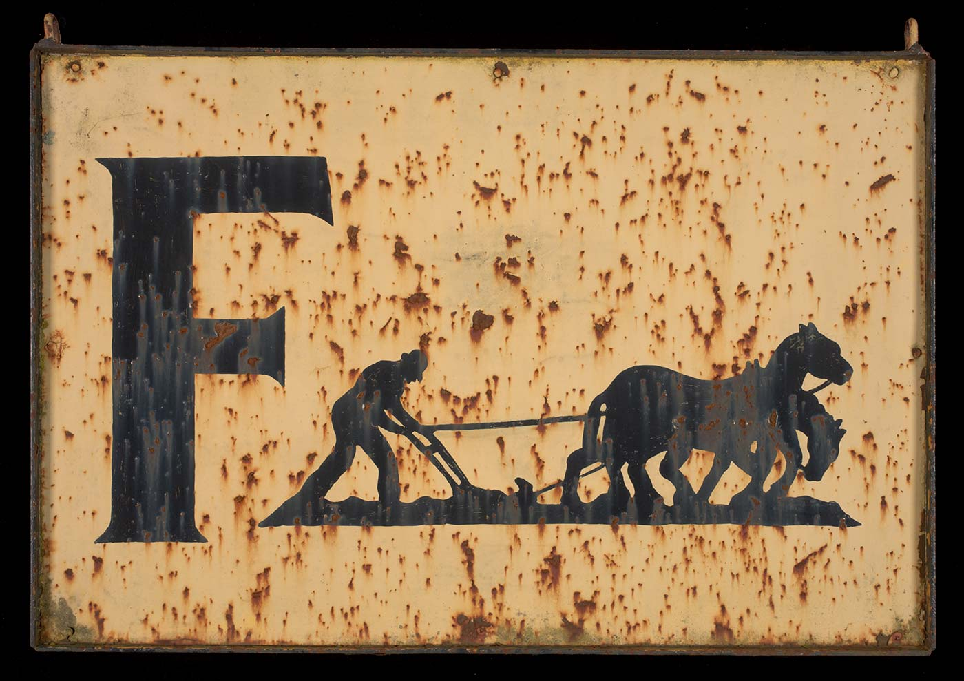 A colour photograph of an old metal sign which appears to be rusting through. On a cream background, the sign begins with a large black capital F followed by a black painted outline of a man operating a horse-drawn plough and two horses. - click to view larger image