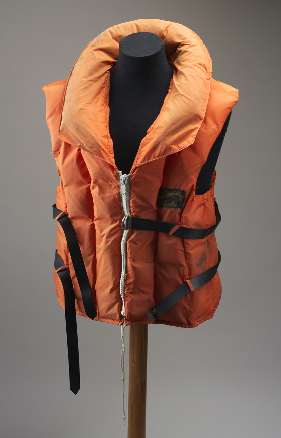 An orange life jacket, mounted on a mannequin. The sleeveless jacket has a collar, a zip at the front and two black straps around the middle. - click to view larger image