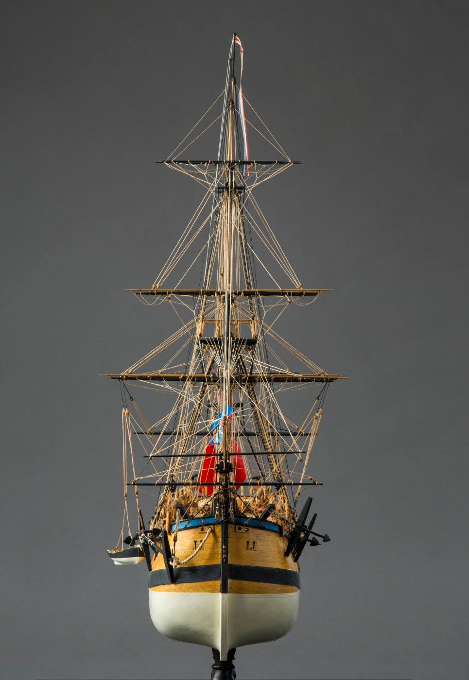Front view of a model wooden sailing ship, with tall masts and rigging, and anchors at front either side. - click to view larger image