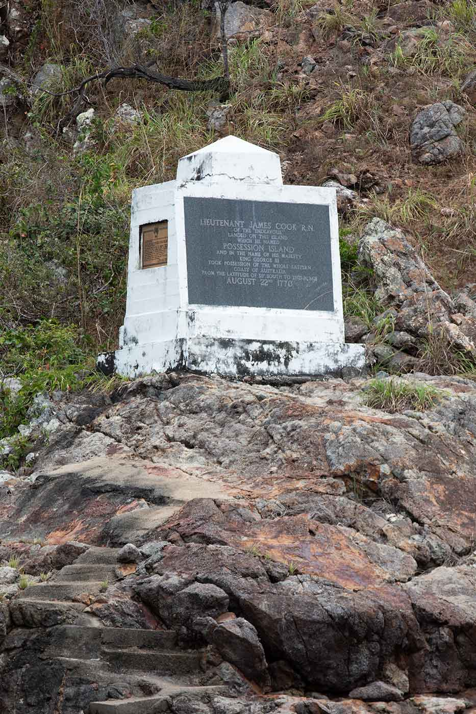 White concrete monument positioned on a rock with a plaque commemorated to Lieutenant James Cook. - click to view larger image