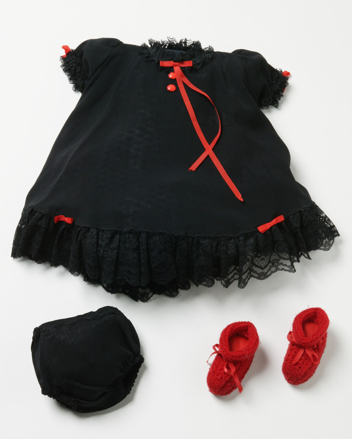 Small black dress with black lace trim at the neck, arms and bottom. Also has two thin red ribbon bows at the bottom and on the arms. Includes matching black bans and a pair of knitted red booties with red ribbon ties at the front. - click to view larger image