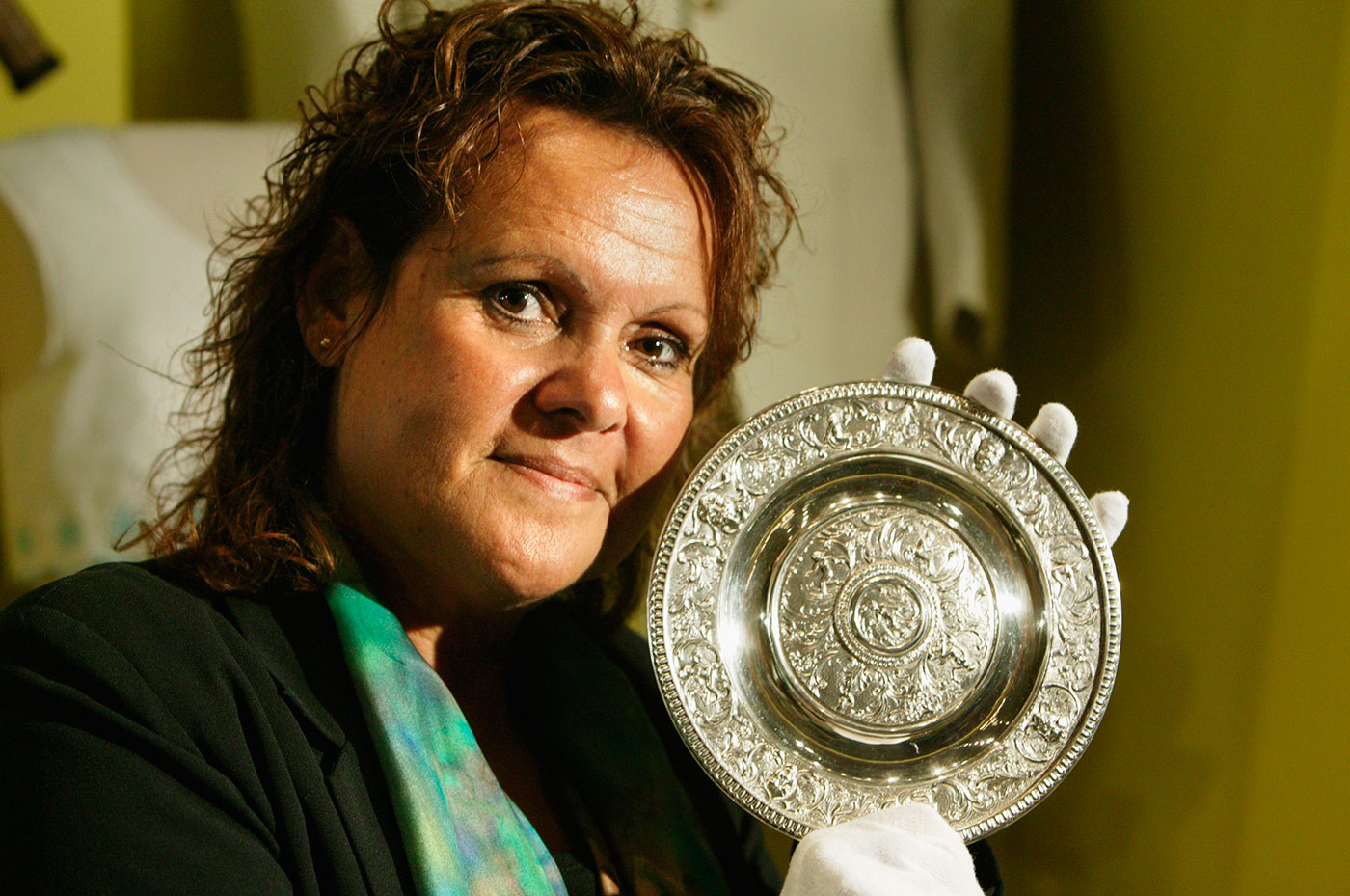 Evonne Goolagong Cawley, wearing white cotton gloves, holds a small silver plate. - click to view larger image