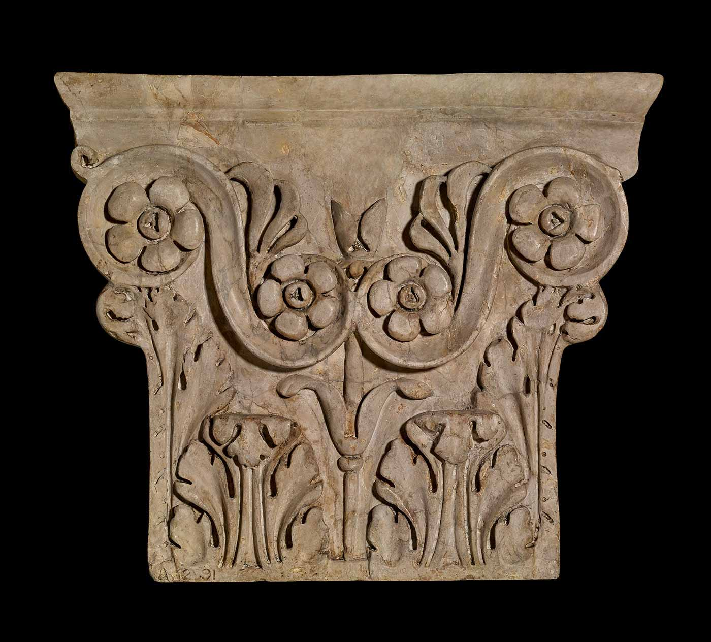 A pilaster capital featuring a floral relief engraving.