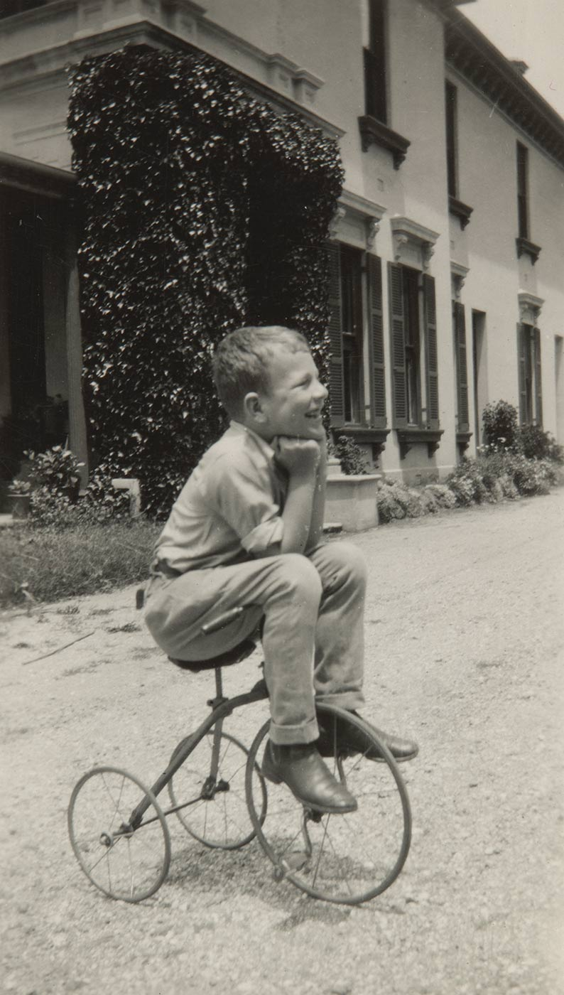 A black and white photo of Andrew Gibson as a child sitting on his tricycle. - click to view larger image