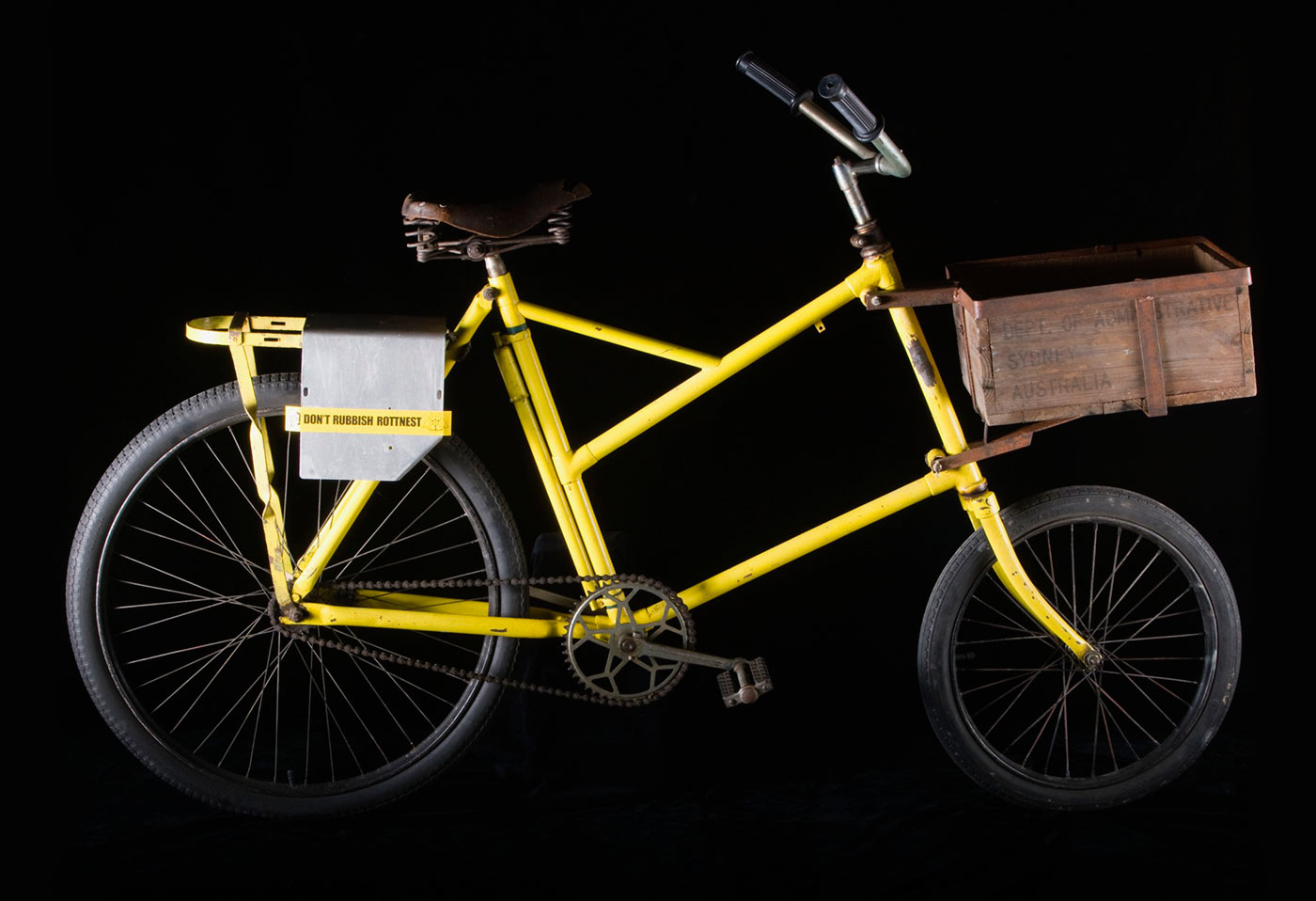 A yellow bicycle with a wooden crate on the front and a small detachable a yellow sticker on the back of the bicycle reads