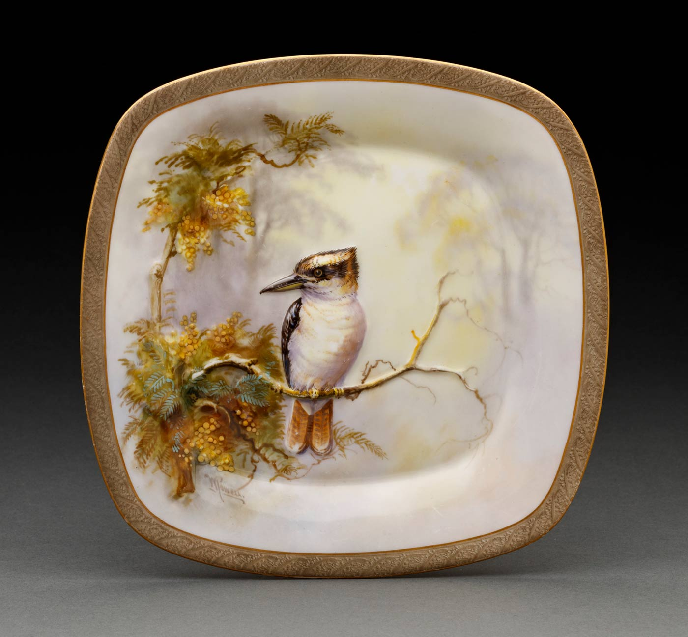 A white square plate embossed and painted with a Kookaburra sitting on a branch with yellow flowers and green leaves against a yellow and purple background, signed on left 'W POWELL' in brown, edges decorated with gold lines and a band of olive green lightly embossed with leaf design, paint missing in some areas. - click to view larger image
