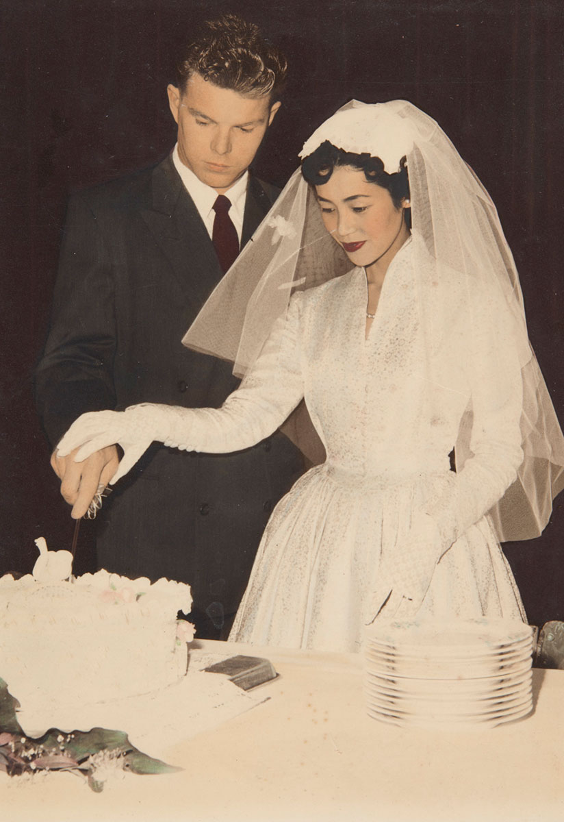 Portrait photograph of Yoshiko Ishikawa and Victor Creagh on their wedding day. They are standing next to each other and cutting their wedding cake. They are both holding the knife, with Yoshiko's hand placed on top of Victor's. Yoshiko wears a long-sleeved cream and metallic silver dress, white gloves and a white veil. Victor wears a dark-coloured suit jacket with a white shirt and deep red tie. - click to view larger image