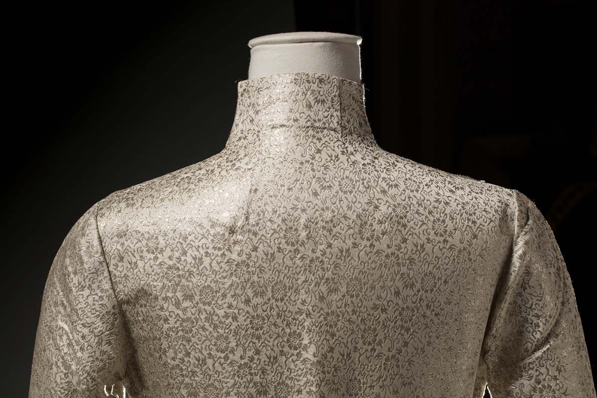 Cropped image of a cream-coloured synthetic brocade dress showing back of neckline and shoulders. - click to view larger image