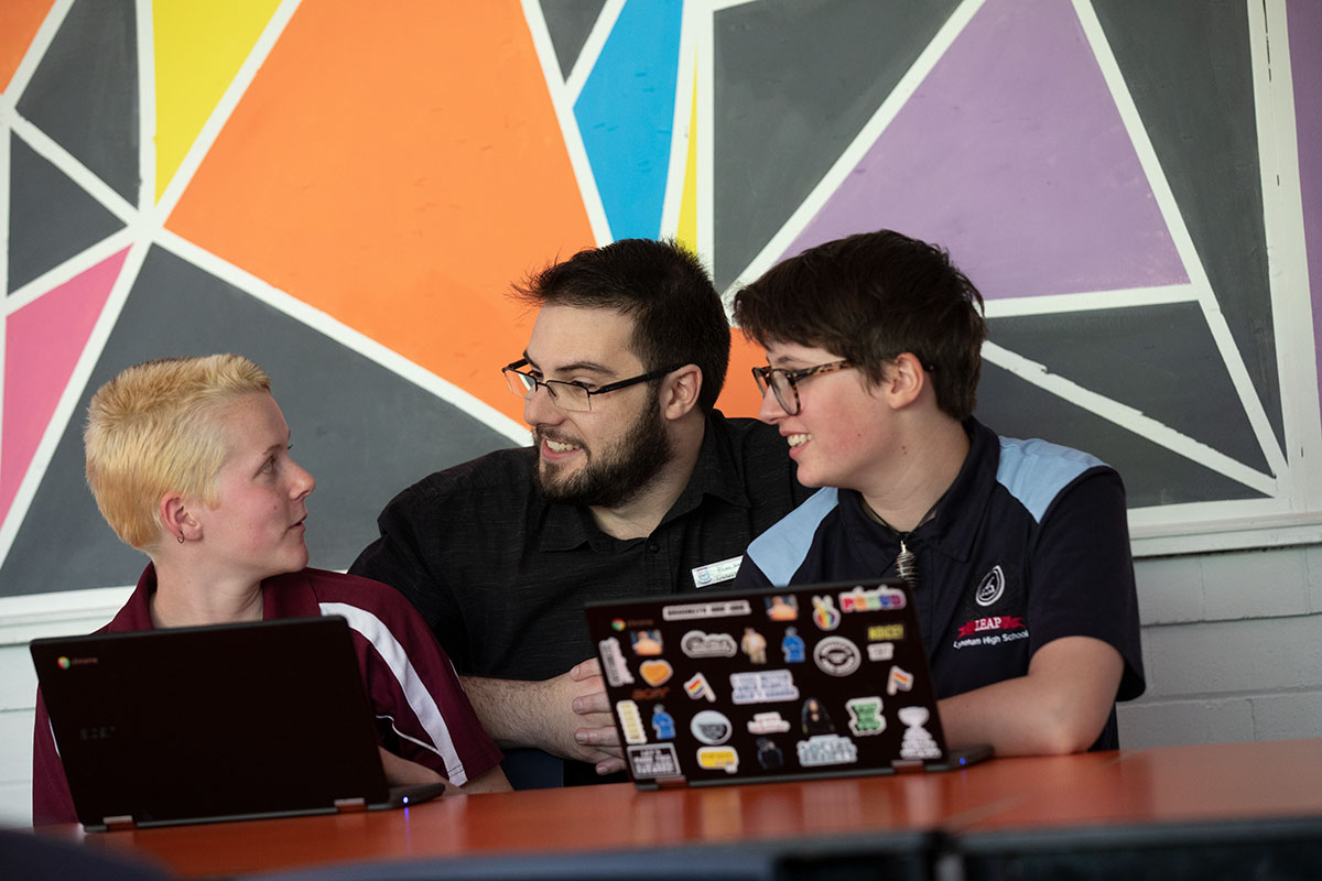 A teacher with two students with laptop computers.