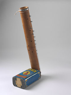 A musical instrument consisting of a bamboo tube with keys and strings down the sides and a blue olive oil tin at the base.
