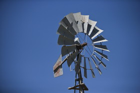 Top section of a windmill, set against a blue sky. Grey blades in a circular formation front a sail with 'SOUTHERN CROSS' painted in red.
