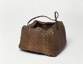 Basket made of pandanus leaves weaved into alternating narrow stripes in a brown or yellowish colour.