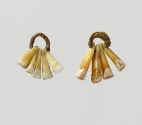 An ear-ornament formed of five human teeth strung on a plaited cord.