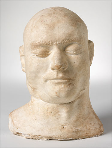 studio photo of a white plaster head. The eyes are closed and the expression appears calm.