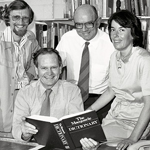 a black and white photo of four people inside an office. There is a bookcase behind them and the man seated is holding a Macquarie Dictionary