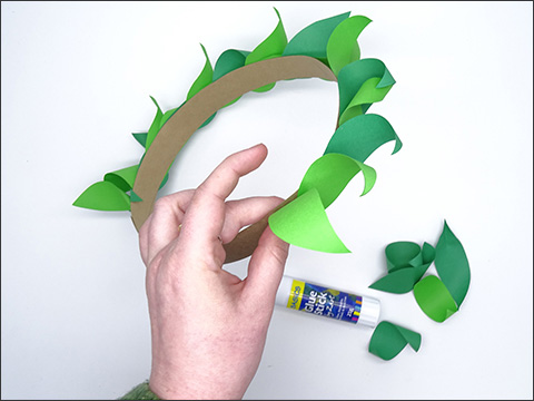 Fingers of one hand grip one part of a headband. The headband is adorned with green paper leaves. There is a glue stick and several pieces of green curled paper to the right of the hand.