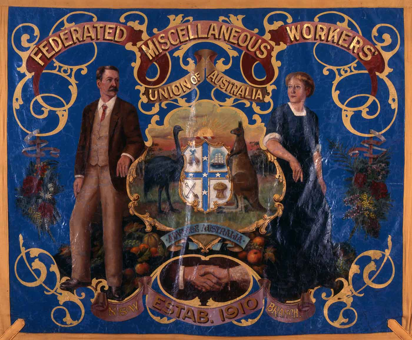 A painted banner with gold fabric border. The banner is painted royal blue with an image of a man and woman leaning on a central image of the coat of arms. 'FEDERATED MISCELLANEOUS WORKERS UNION OF AUSTRALIA' is painted in gold at teh top of the banner.