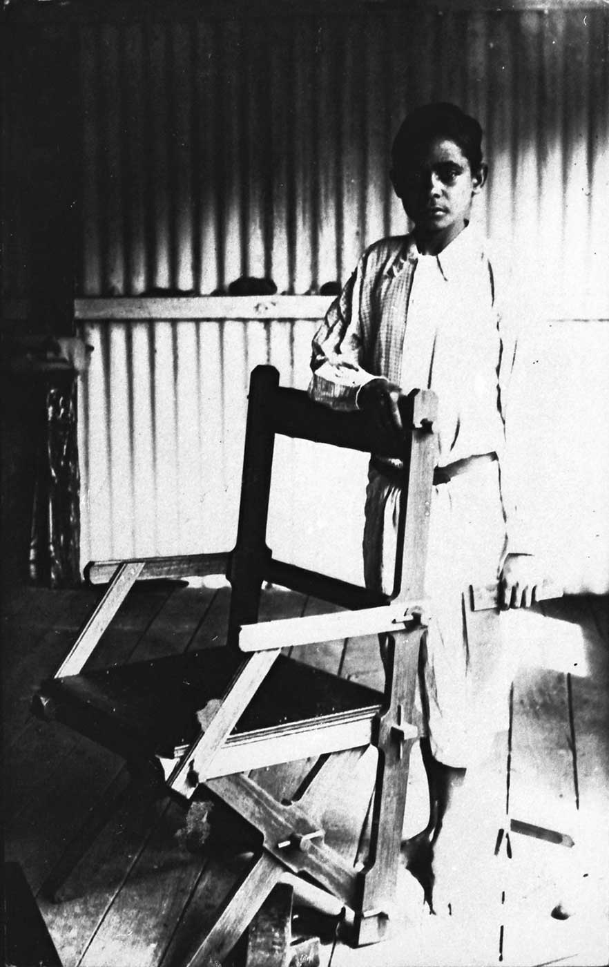 Black and white photograph of a boy standing behind a wooden chair. The boy is dressed in a shirt and short pants and is barefoot.