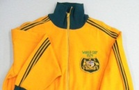 Top section of a gold tracksuit with green trim and the Australian coat of arms on the right breast.