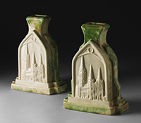 Two cream glazed ceramic vases shaped as Gothic arches on a rectangular base, with buttresses at two sides. The front shows the relief image of a church with three spires.
