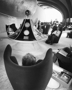 Black and white image showing people sitting in high-backed winged chairs. A circular display case, which rises to a peak is also visible.