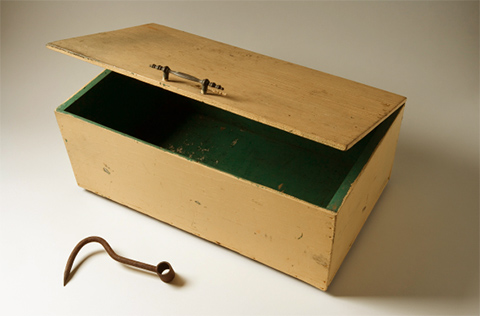 Image of a yellow box painted green inside and a rusted hook.