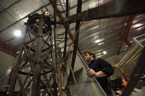 A man holds a piece of galvanised steel to a large metal windmill frame.