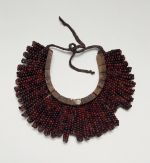 Breast plate, formed into a crescent-shaped base made of light soft wood tied together. The breast is covered over with the beautiful red and black tropical peas.